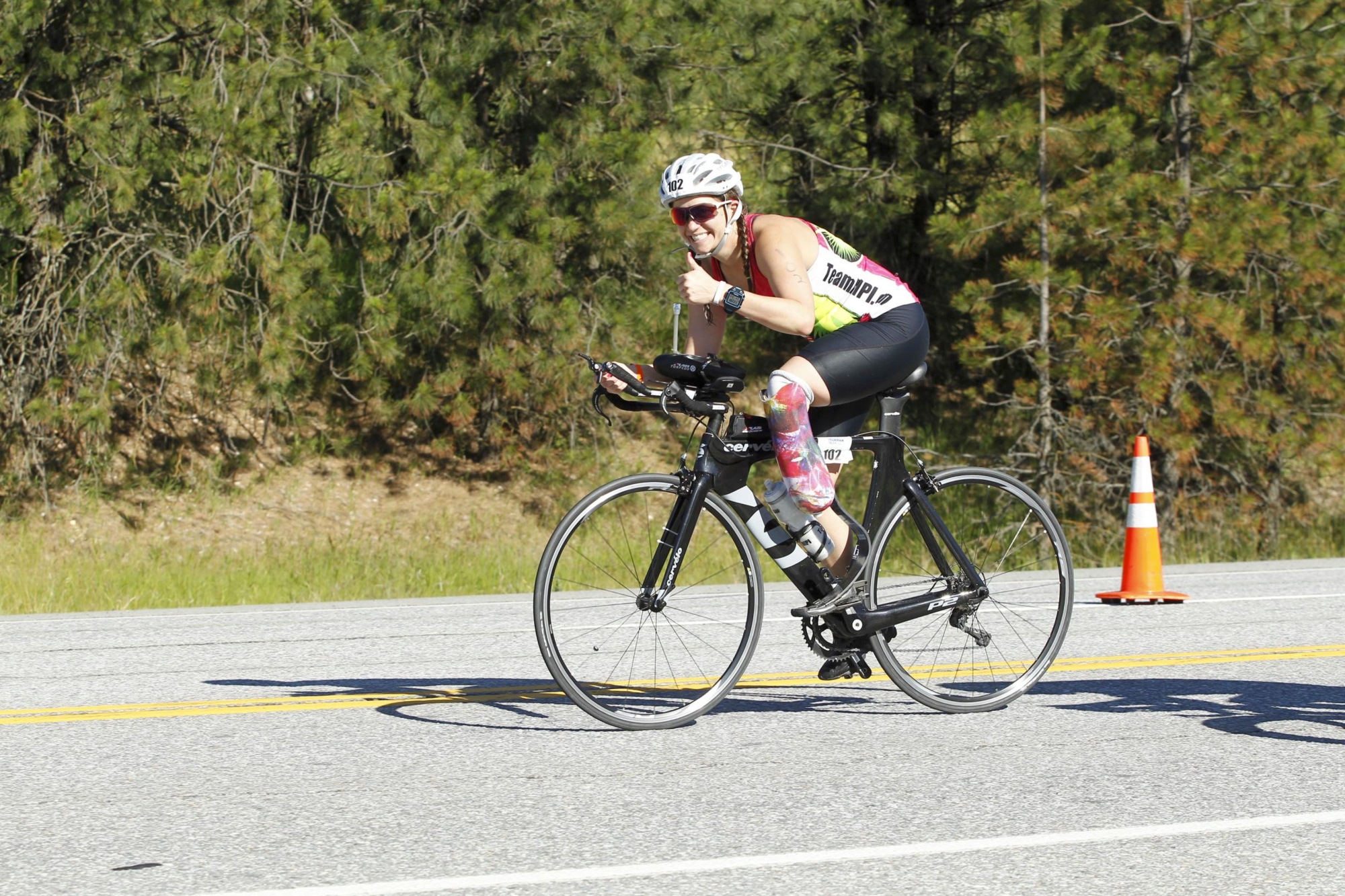 Emily on her bike giving the camera a thumb's up while on course at IM70.3 Coeur d'Alene in June of 2016