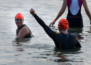 Becky and I in the water at the swim start - me smiling and Becky with her hand in the air cheering