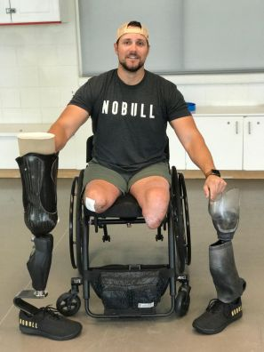 "Craig sitting in a wheelchair holding two prosthetic legs, one on each side of him, and wearing a shirt that says ""no bull"""