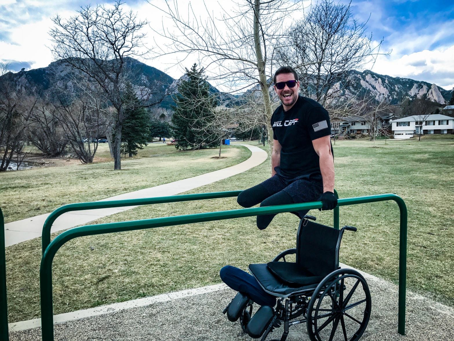 Craig holding himself up in parallel bars in a park with his wheelchair below him