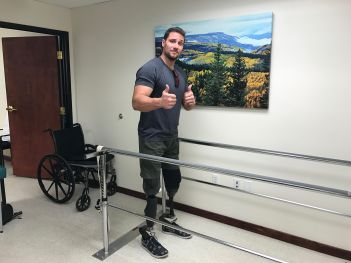 Craig standing between parallel bars wearing prosthetic legs and giving the double thumbs up