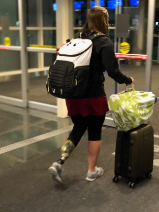 Emily walking at the airport with a backpack on her back and her rolling suitcase with her bag of legs attached on top