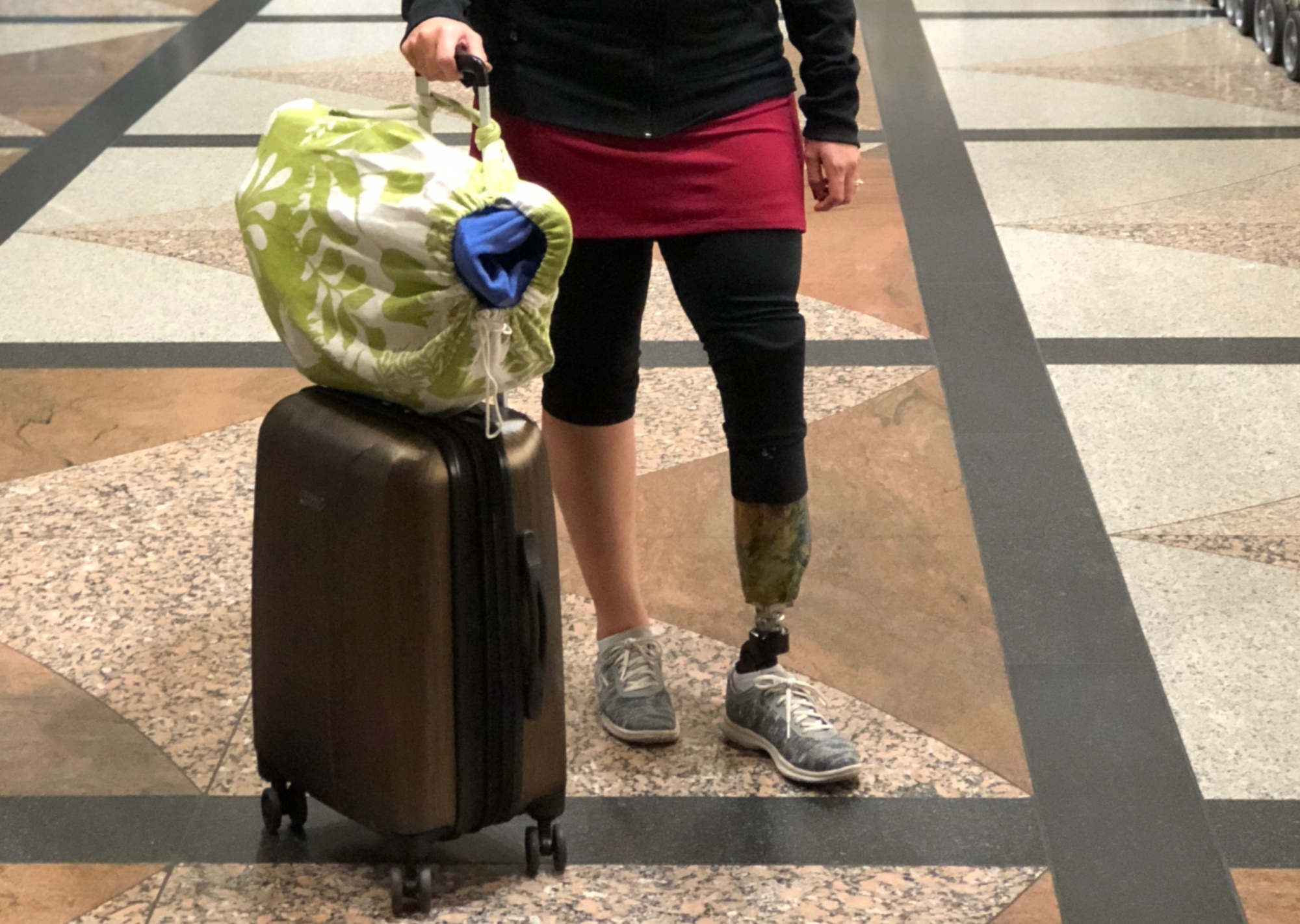 Emily standing at the airport with her rolling suitcase and bag of legs on top