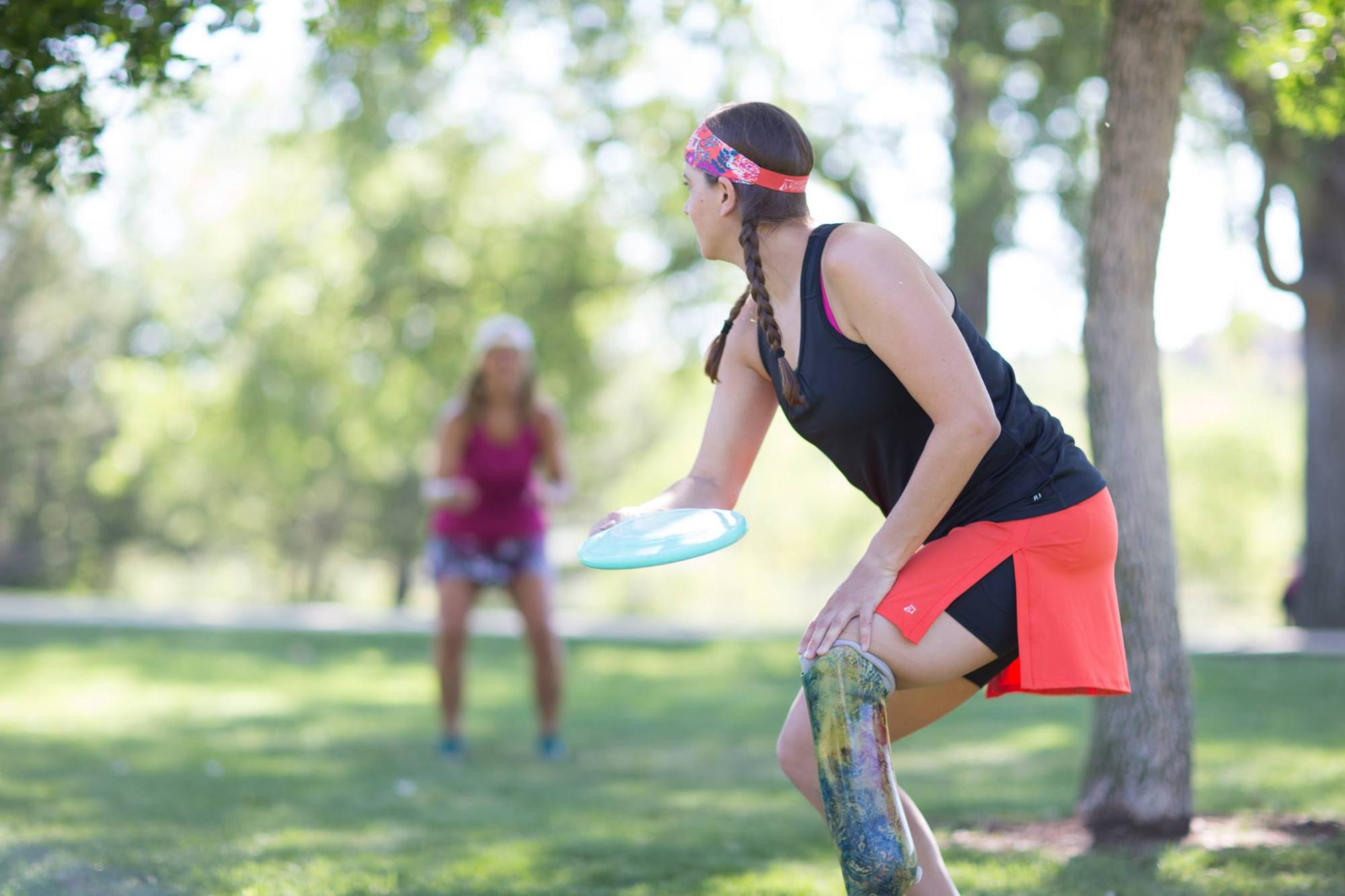 Emily during Skirt Sports modeling shoot, throwing frisbee to another model (Jenn) who is blurry in the background. photo credit: Kim Cook