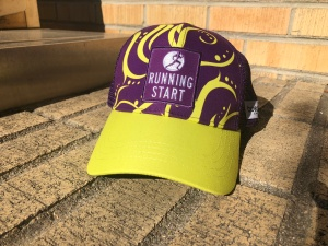 Purple & yellow trucker hat with Running Start logo on bricks