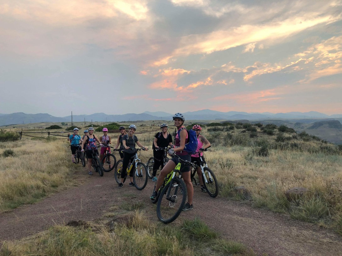 Group of women with mountain bikes with a beautiful sunset over the mountains in the background