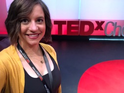 Me after hair and makeup standing in front of the TEDx letters
