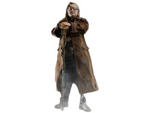 Mad-Eye Moody standing and holding his walking stick/wand, wearing brown cloths, showing his prosthetic leg slightly