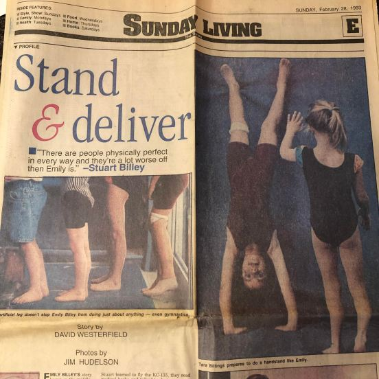 """Front page of Section E of The Shreveport Times, Stand & Deliver, """"There are people physically perfect in every way and they're a lot worse off than Emily is."""" - Stuart Billey, Story by David Westerfield, Photos by Jim Hudelson. Photo 1 of little kid legs, including my prosthesis, standing in a line. Photo 2: me doing a handstand and another blonde girl about to do one next to me."""