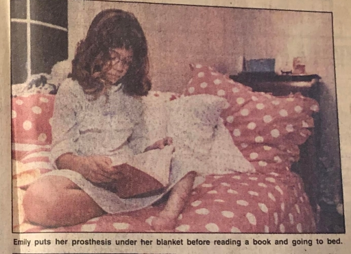 """Photo of me reading in my bed with text below that reads, """"Emily puts her prosthesis under the blanket before reading a book and going to bed."""""""