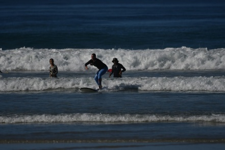 me standing on the surfboard with friend Pia in the background and instructor Nego watching