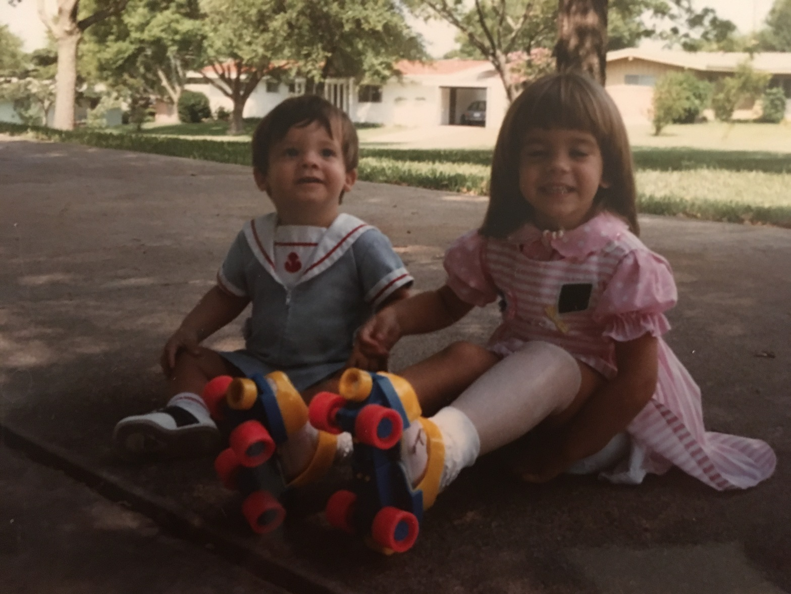 Toddler Sam and Young Emily wearing roller skates and sitting on the sidewalk