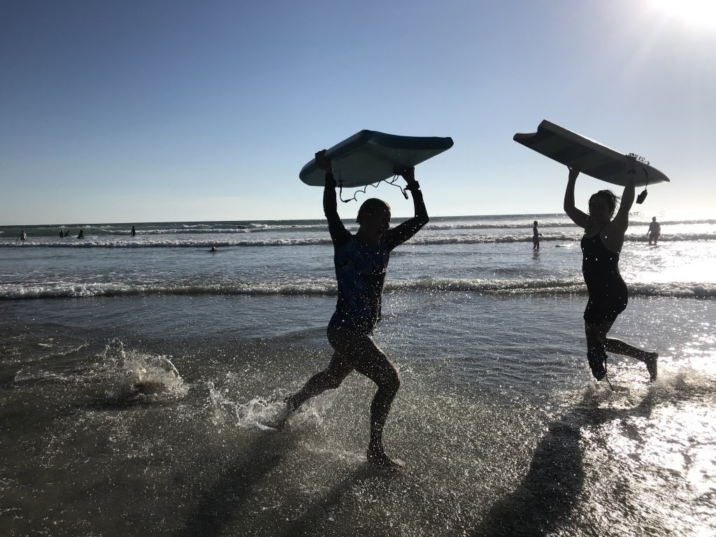 Silhouette of Nicole and I running in the water's edge holding boogie boards above our heads