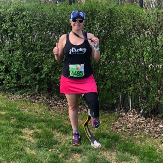 Me giving a thumb's up and holding my medal out to the side. I'm wearing my running, a pink running skirt, a black tank top that says